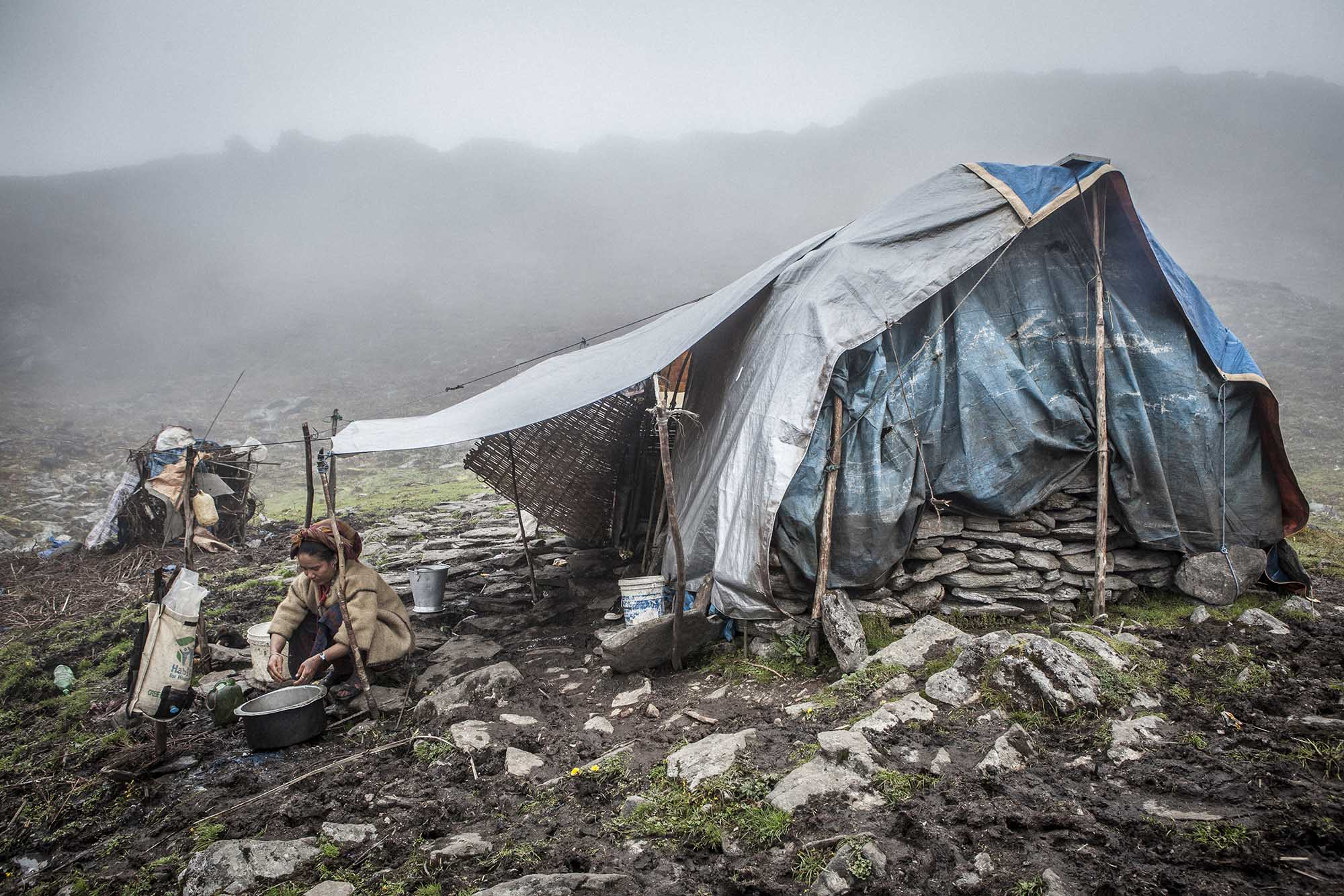 Maili Ghising is washing the dishes in her temporary shelter located at Panch Pokhari, 4300 meters in altitude. Sindhupalchowk, Nepal. 2015.