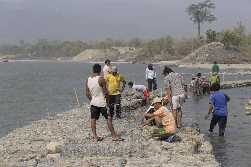 Workers rebuild gabion wall to replace the vulnarable old wall to protect villages from flood at Koshi Barrage. Sunsari, Nepal.