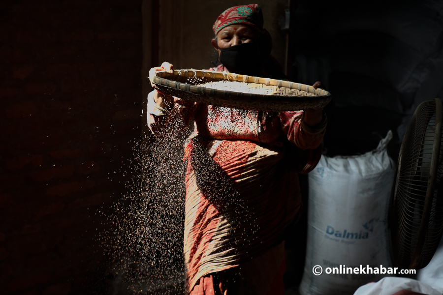 A woman separating hays from mustard seeds